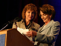 APME president Karen Magnuson hands Speaker Pelosi a note during her speech at the 2007 APME conference in Washington, saying that the Senate Judiciary Committee had just approved a national press shield bill. Photo by James K. Sanborn